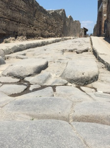 These stone streets were actually meant to transport human waste - the three stones sticking out of each section were pedestrian cross areas.